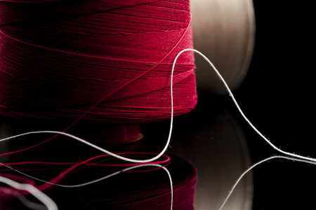 Foto de common thread, cotton yarn red and white leaning on black table mirror. reel of cotton spool of red and white cotton blurred in the background - Imagen libre de derechos