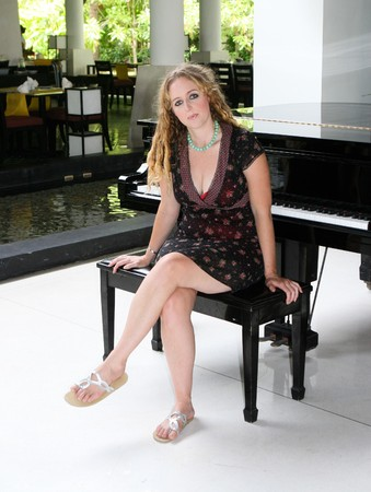Pretty blond piano player next to a piano.