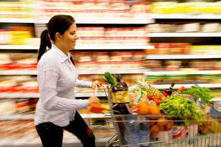 Young woman with shopping cart in the supermarket when shopping