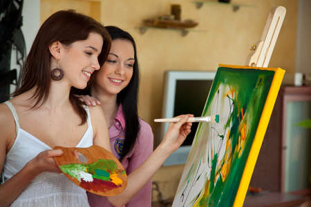 Young woman paints in her spare time with oil paints on a easel