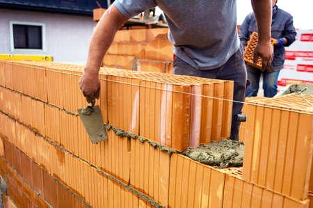 Foto de construction workers at the walls of a shell in solid construction  brick wall of a detached house - Imagen libre de derechos