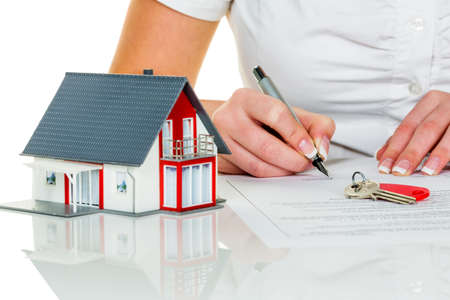 Photo for a woman signs a contract to purchase a home with a real estate agent. - Royalty Free Image
