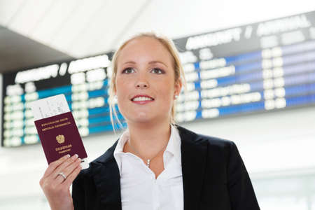 woman with passport and airline tickets at an airport waiting for her departure on holiday