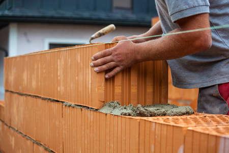 Foto de anonymous construction worker on a building site when building a house built a wall of bricks.  - Imagen libre de derechos
