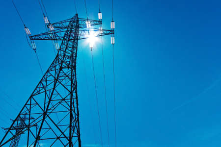 Foto de the power pole high-voltage lines with sun and blue sky. energy supply by power line. - Imagen libre de derechos