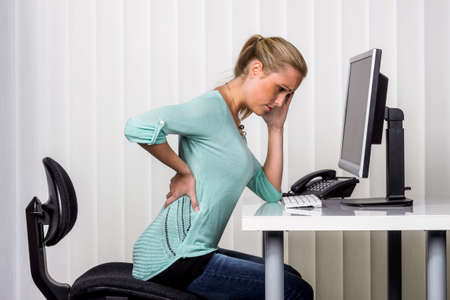 Photo for a woman sitting at a desk and has pain in her back. photo icon for proper posture at work in the office. - Royalty Free Image