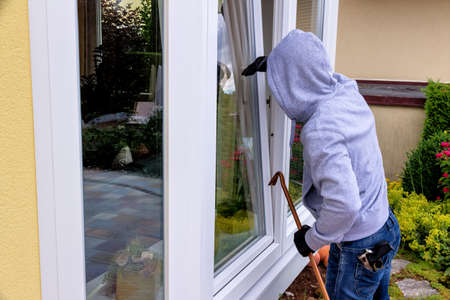 Photo for a burglar trying to break in an open window with a crowbar - Royalty Free Image