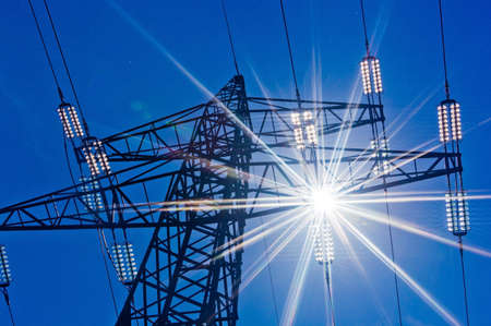 Foto de a high voltage towers for power against blue sky and sun rays - Imagen libre de derechos