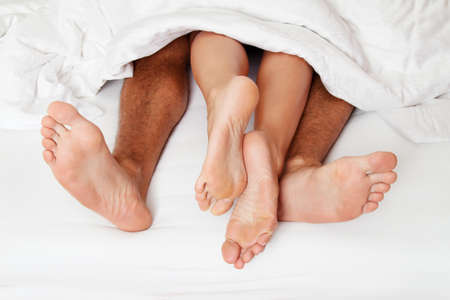Foto de A couple feet in bed. love, eroticism and partners. - Imagen libre de derechos