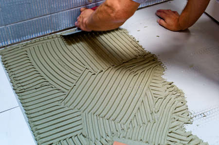 Photo pour a tiler at work. sticking of floor tiles with tile adhesive and spatula. - image libre de droit