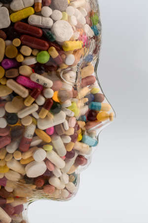 Photo pour a head made of glass filled with many tablets. photo icon for drugs abuse and painkillers. - image libre de droit