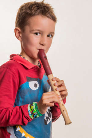 Photo for a child playing on a flute on wood. music education and music school. - Royalty Free Image