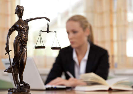 Photo pour a young lawyer is sitting at her desk in the office - image libre de droit