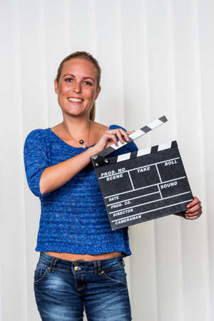 Photo for a woman holds a typical clapperboard in her hand - Royalty Free Image