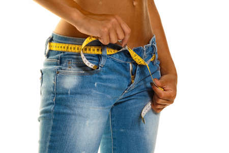 Foto de a young, slim woman in jeans with a tape measure after a successful diet - Imagen libre de derechos