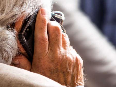 Photo pour senior is talking on a mobile phone - image libre de droit
