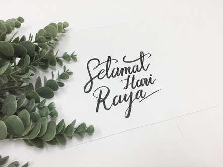 Photo for Card written Selamat Hari Raya (Happy Eid) on white paper against white background with eucalyptus plant - Royalty Free Image