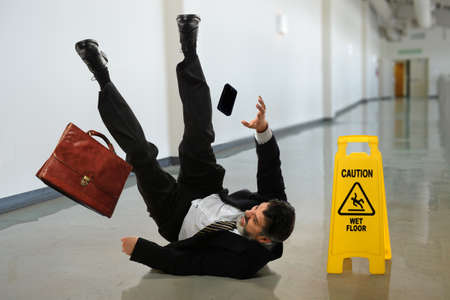 Foto de Senior businessman falling near caution sign in hallway - Imagen libre de derechos