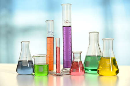 Foto de Laboratory glassware with liquids of different colors on white table - With clipping path on glass - Imagen libre de derechos