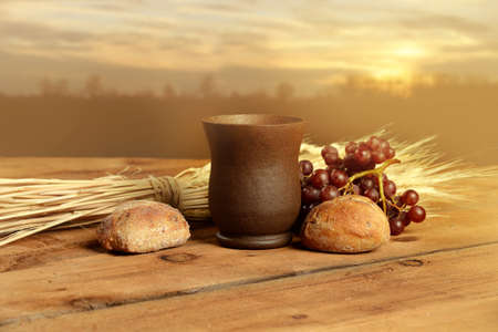 Foto de Cup of wine, bread. grapes and wheat on vintage table with warm sunset in background - Imagen libre de derechos