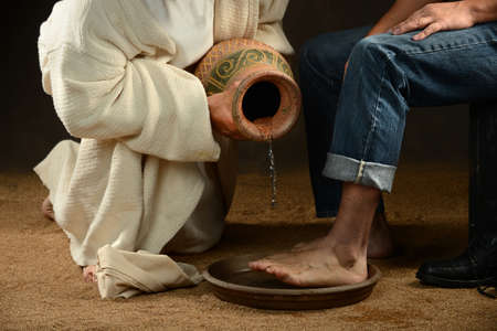 Photo for Jesus pouring water to wash feet of modern man over dark background - Royalty Free Image