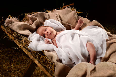 Photo for Baby Jesus when born on a manger wrapped in swaddling clothes over dark background - Royalty Free Image