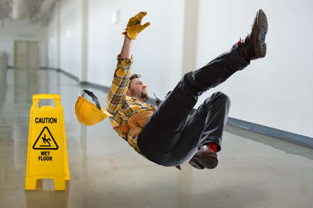 Foto de Worker falling on wet floor inside building - Imagen libre de derechos