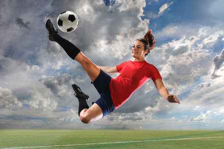 Photo for Female soccer player kicking ball outdoors - Royalty Free Image