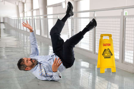 Photo pour Hispanic businessman falling on wet floor inside office building - image libre de droit