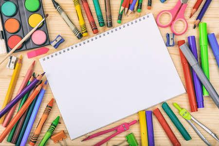 Photo pour School supplies on wooden background - space for caption - image libre de droit