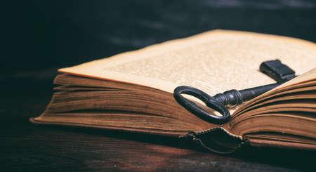 Foto de Key to knowledge concept. Key on a vintage book on wooden background - Imagen libre de derechos