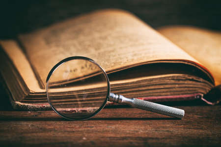 Photo for Vintage book and magnifying glass on wooden background - Royalty Free Image