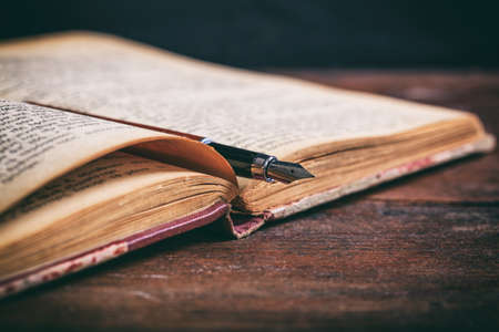 Photo for Open vintage book and ink pen on a wooden desk - Royalty Free Image