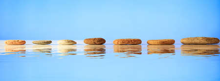Photo pour Zen stepping stones on blue background, reflections on the water - image libre de droit
