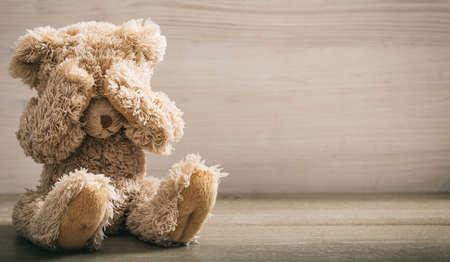 Foto de Child abuse concept. Teddy bear covering eyes in an empty room - Imagen libre de derechos