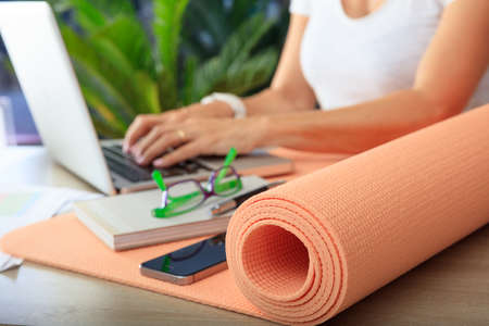 Foto de Relax at work concept. Yoga mat in an office desk - Imagen libre de derechos
