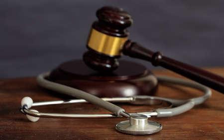 Foto de Law gavel and a stethoscope on a wooden desk, dark background - Imagen libre de derechos