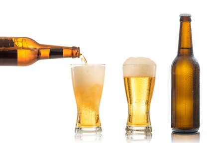 Foto de Bottles and glasses of beer on white background. Pouring beer into one glass - Imagen libre de derechos