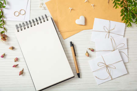 Foto de Wedding invitations preparation. Flat lay and top view of to-do list and wedding invitations on a white wooden tabletop, copy space. - Imagen libre de derechos