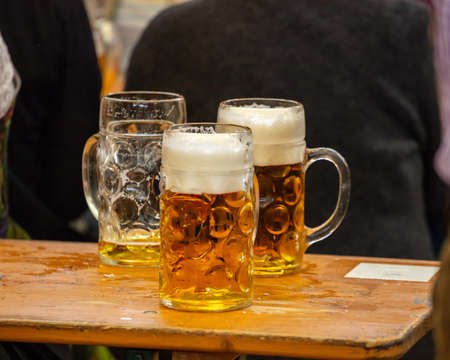 Foto de Mugs of Bavarian beer on a wooden desk, closeup view. Oktoberfest, Munich, Germany. - Imagen libre de derechos