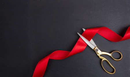 Photo pour Grand opening. Top view of gold scissors cutting red silk ribbon against black background, copy space - image libre de droit
