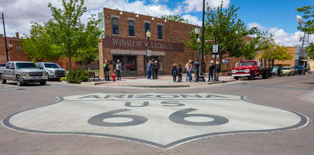 Photo pour Winslow Arizona, US. May 23, 2019. Historic route 66 sign on the street, Tourists looking at the Standin on the corner statue, - image libre de droit