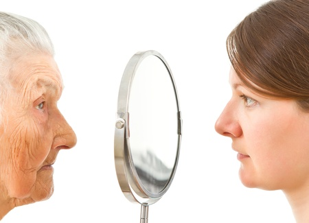 Foto de young and old  isolated faces standing on the two sides of the  mirror - Imagen libre de derechos