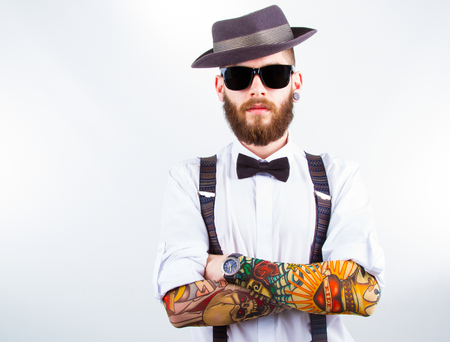 Photo pour young hipster man wearing  hat , suspenders,  bow-tie and a funny tattoo-sleeve - image libre de droit