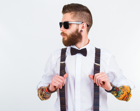 Photo pour young hipster man holding his suspenders with   funny tattooed sleeves - image libre de droit