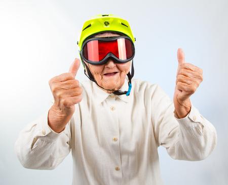 Foto de funny grandma wearing a yellow bicycle helmet and ski  goggles and showing thumbs up - Imagen libre de derechos