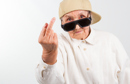 Photo pour Funny grandma's studio portrait  wearing eyeglasses and baseball cap, who shows her f-finger ,  isolated on white - image libre de droit