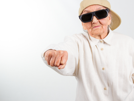 Foto de Funny grandma's studio portrait  wearing eyeglasses and baseball cap who kicks with  her fist , isolated on white - Imagen libre de derechos
