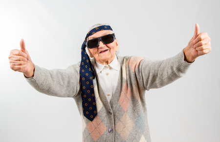 Foto de Funny grandma's studio portarit with a tie on her forehead, showing thumbs up - Imagen libre de derechos