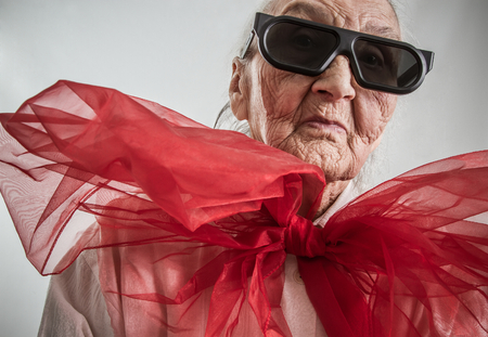 Foto de stylish grandma with eyeglasses and  a huge red  bow on her neck - Imagen libre de derechos